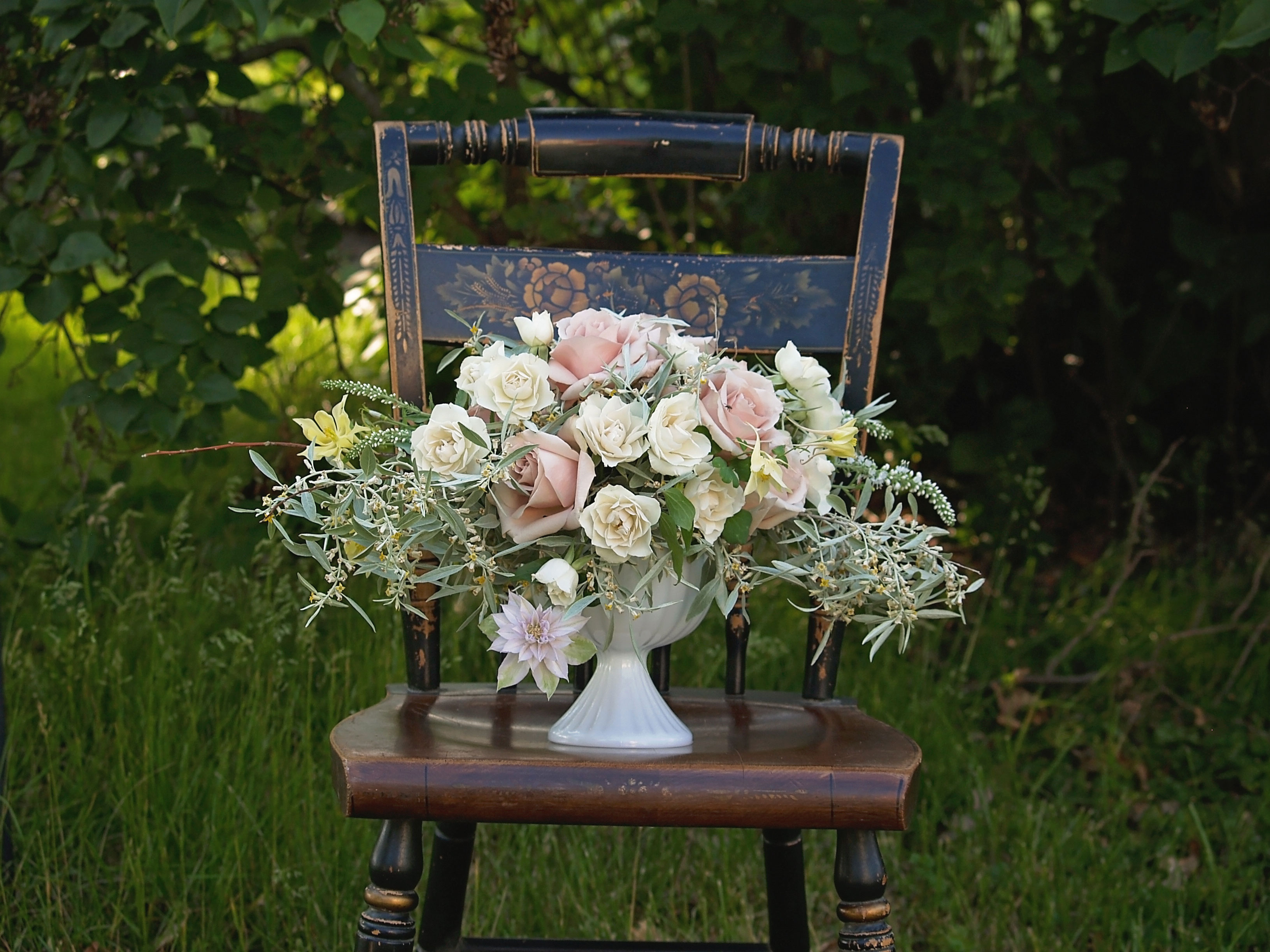 rustic compote centerpiece in pastel shades in milk glass vase on vintage chair