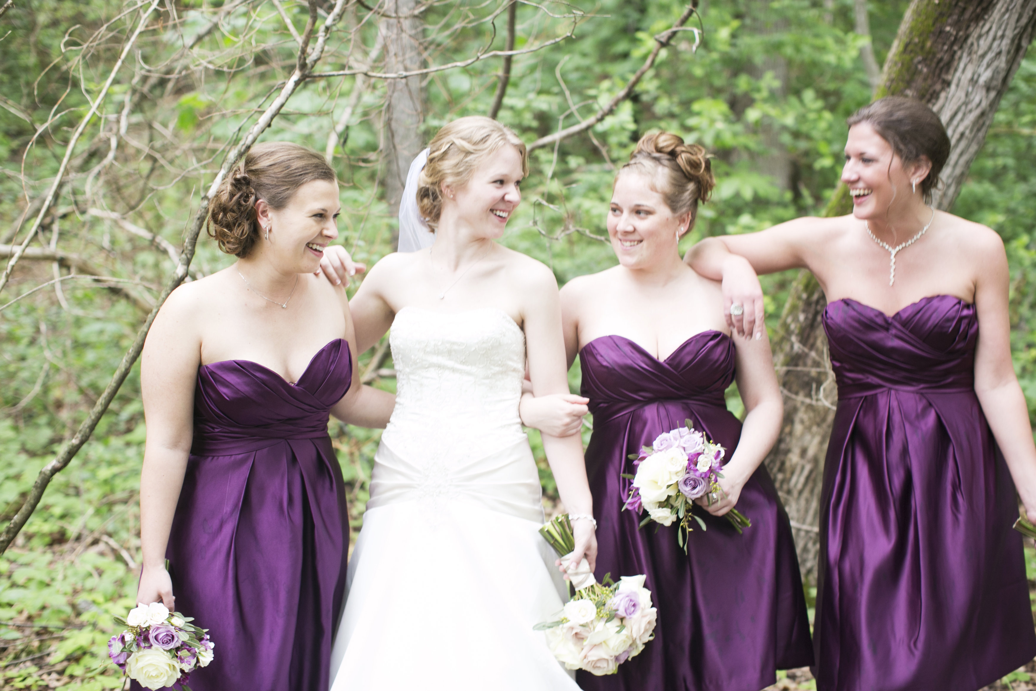 smiling bride, happy bridesmaids in purple dresses with bouquets
