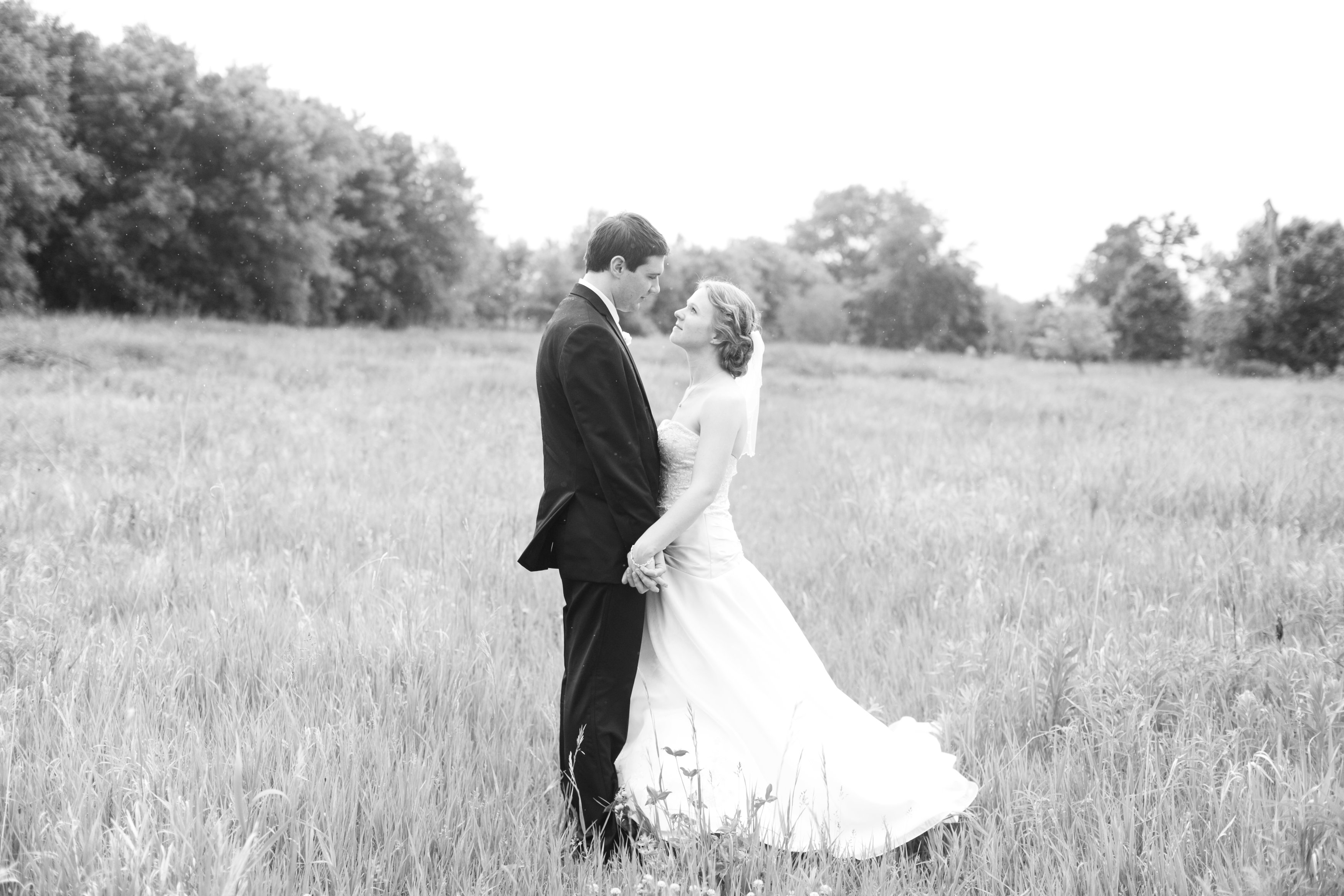 black and white photo of bride and groom in a field