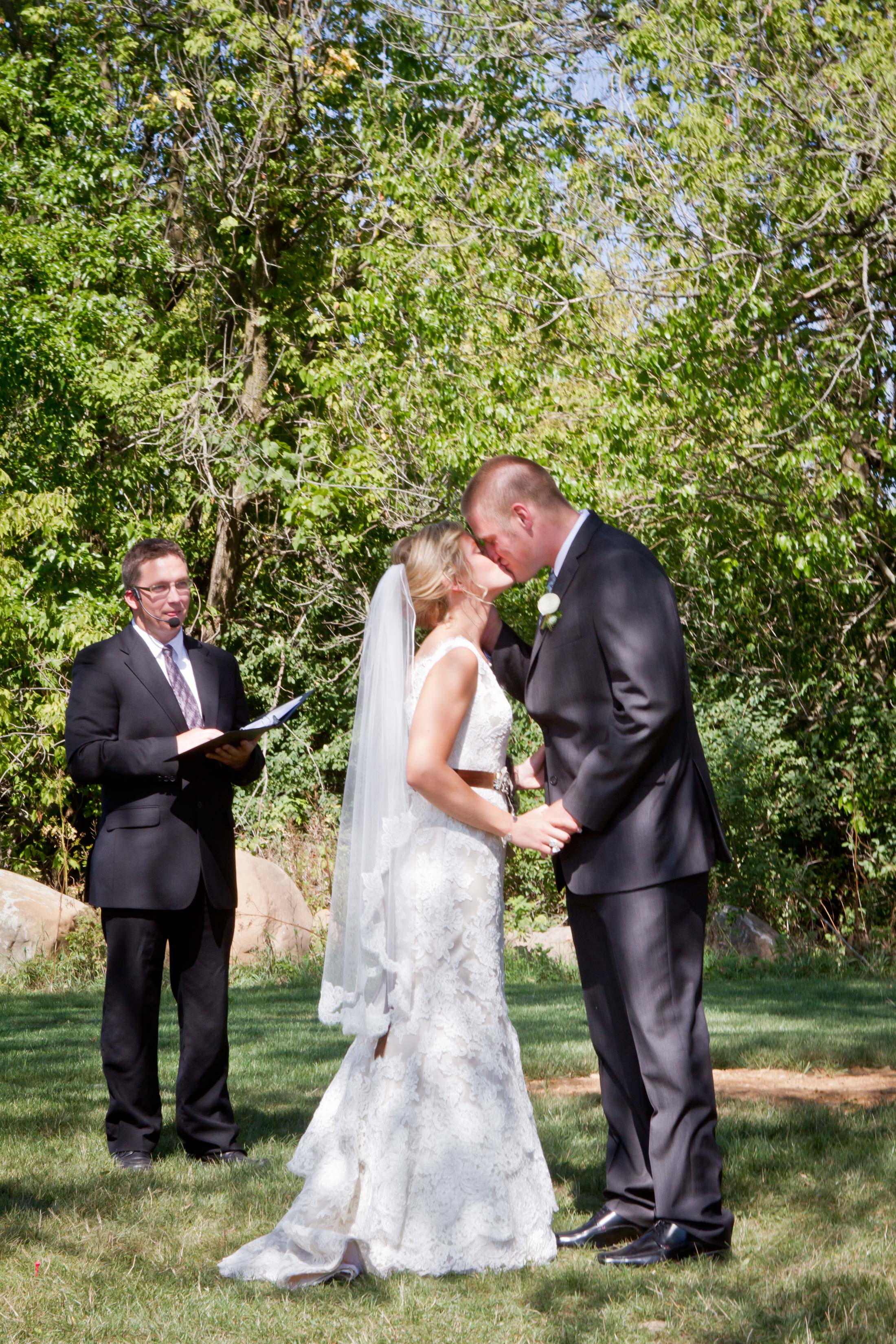 bride and grooms first kiss at barn at harvest moon pond