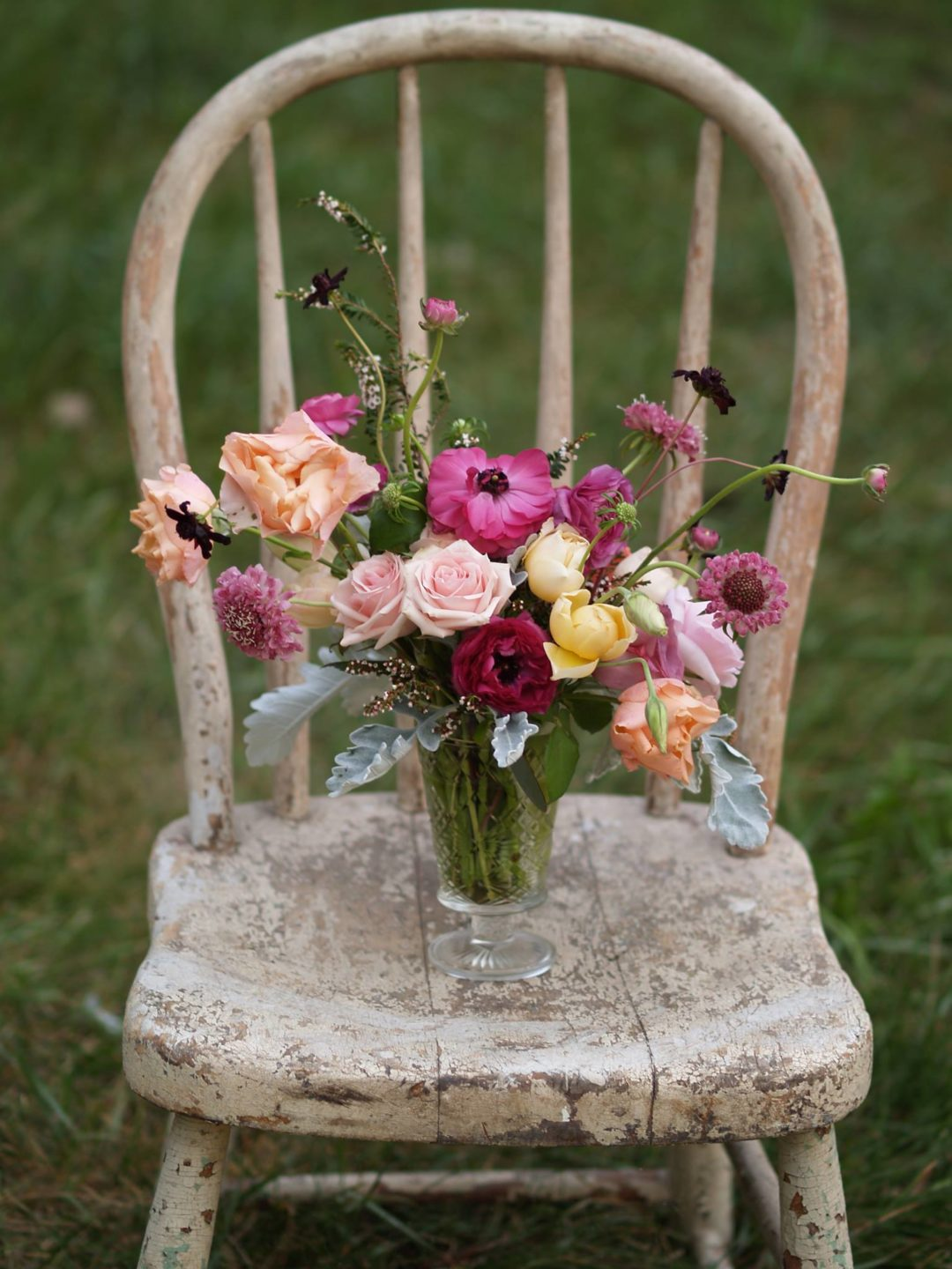 wild whimsical centerpiece in bright colors on old chipped paint chair