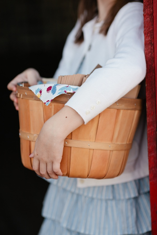 girl carrying apple basket with wedding programs