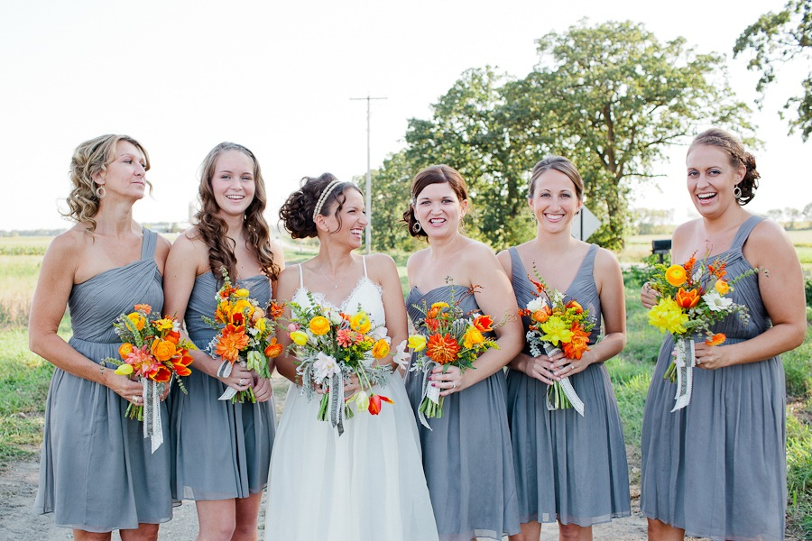 bridesmaids with gray dresses and bright orange and yellow bouquets