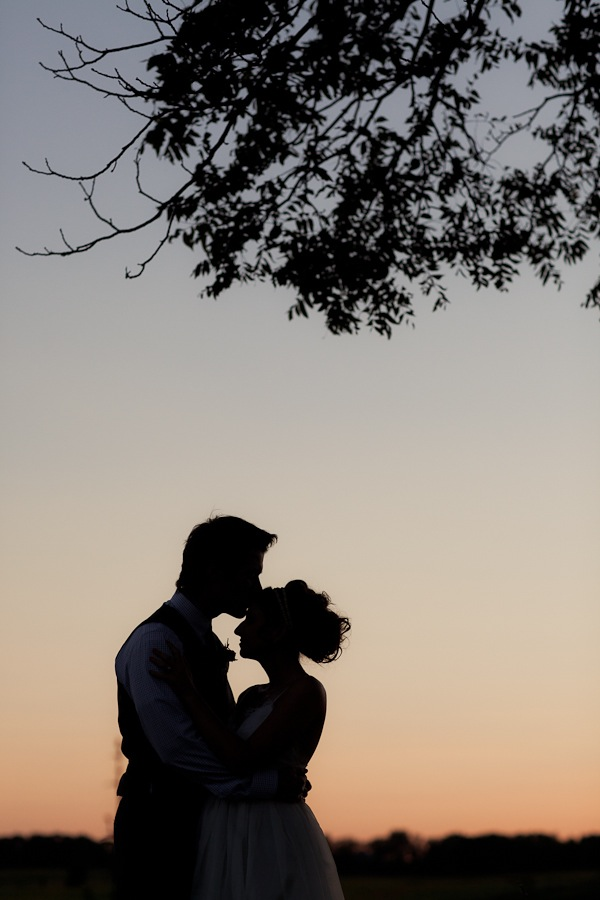 bride and groom shadows kissing at sunset