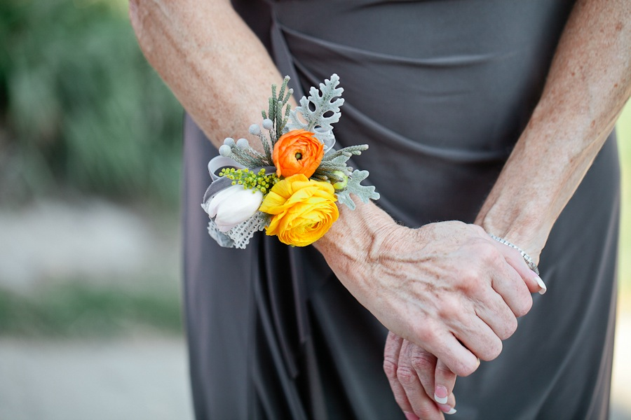 bright ranunculus wrist corsage orange yellow and white