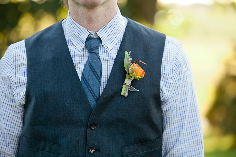 orange ranunculus boutonniere on a gray vest