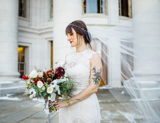 Alluring Blooms Madison WI bride holding a winter inspired bouquet on the steps of the state capitol building with veil blowing in the wind