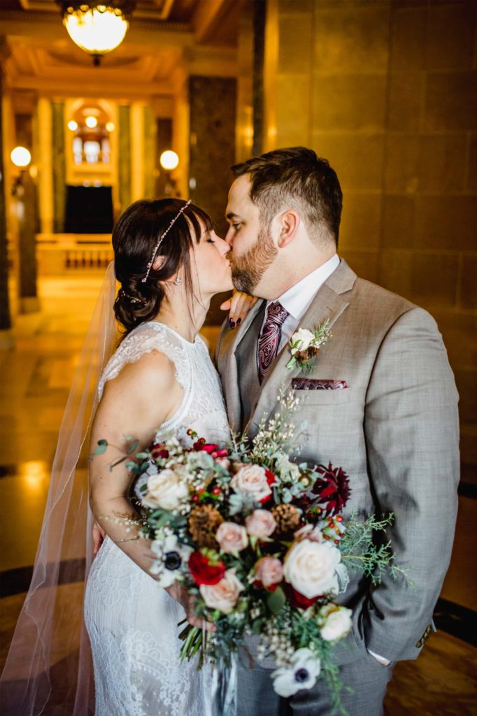 bride and groom kissing with winter wedding bouquet Madison WI Alluring Blooms Florist