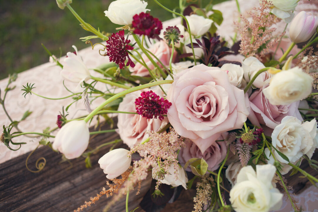 Lush garden inspired valentine's blooms including blush pink roses and astilbe, burgundy scabiosa and white tulips