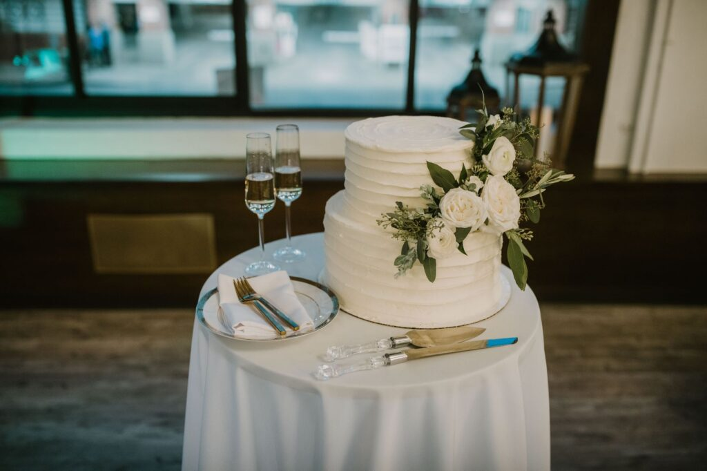 two layer cake with simple frosting and white floral and eucalyptus accent