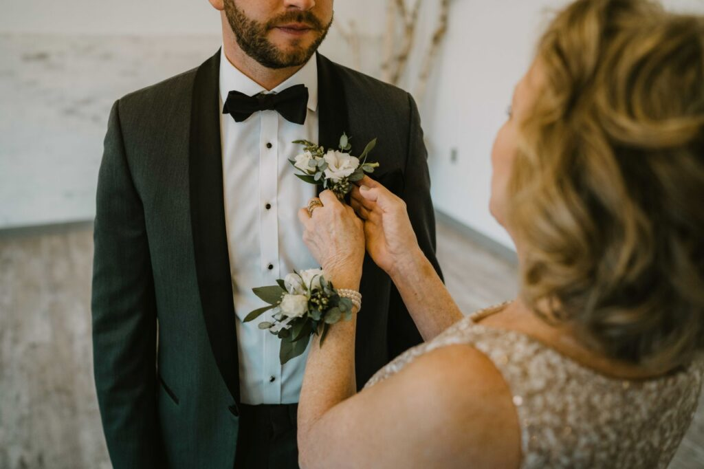 mother wearing pearl bracelet wrist corsage and pinning grooms boutonniere of white flowers