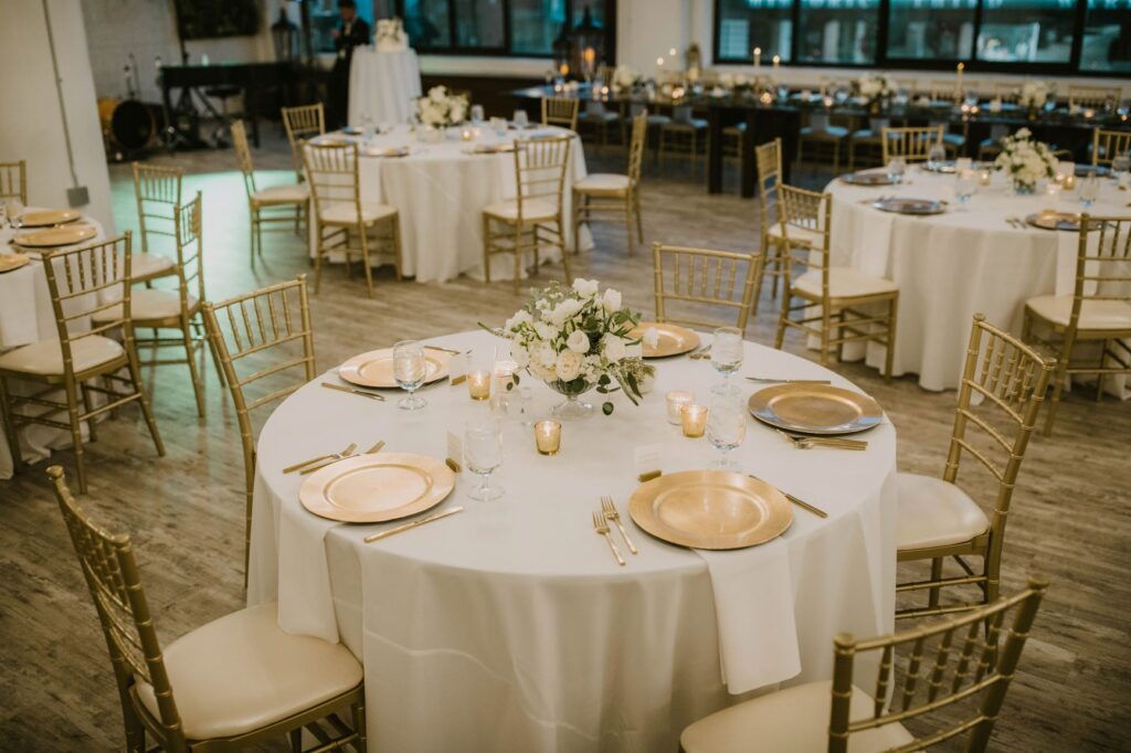 clear compote with white floral on an elegant table set with gold chargers and gold Chiavari chairs